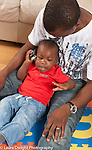12 month old baby boy sitting in father's lap pretend play holding telephone to his ear vertical
