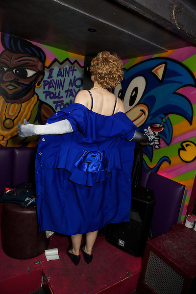 Margaret Thatcher impersonator Honey Wilde strips out of a blue suit at Maggies Nightclub in Chelsea
