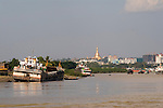 Swedagon Pagoda dominates the city skyline, according to tradition it is 2,500 years old; the oldest pagoda in the world. Souvenirs for the mainly local pilgrims clutter one of the many entrances to the pagoda.  Shwedagon Paya as seen from the  Ayeyarwady ( Irrawaddy) river Myanmar Burma 2011.