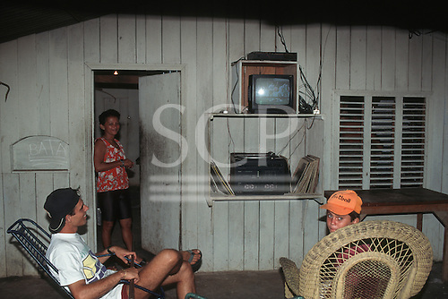 Amapa State, Brazil. Poor rural family outside their wooden shack house watching a television; sound system and vinyl records.