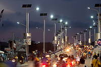 A busy bridge is illuminated by solar powered street lamps.