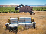 Weathering stuffed couch sitting in the yard of an abandoned house ghost town of Beowawe, Nevada