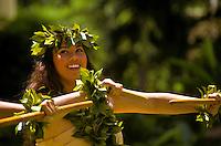 Hula (kahiko) dancer with two kalaau sticks and wearing maile (leaf) lei, Lei Day celebration at Hilton Hawaiian Village Hotel