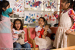 Preschool Headstart 3-5 year olds group of girls in pretend play area talking and pointing wearing dressup clothes horizontal