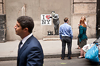 """People walk by and discuss work that appears to be by incognito street graffiti artist Banksy on a wall near Ground Zero and Wall Street in New York, USA, 17 May 2010. The British artist is said to be in New York to promote his movie about street art, """"Exit Through the Gift Shop"""". Several pieces of artwork have been sighted around the city today."""