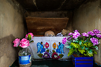 """A dried-up scull is seen wrapped in a painted cloth and placed in a wooden crate inside a niche at the cemetery in Pomuch, Mexico, 26 October 2019. Every year on the Day of the Dead, people of Pomuch, a small Mayan community in the south of Mexico, visit the cemetery to take part in a pre-Hispanic tradition of cleaning of bones of their departed relatives (""""Limpia de huesos""""). People who die in Pomuch are firstly buried for three years in an above-ground tomb then the dried-up bodies are taken out, bones are separated, wrapped in a decorated cloth, put into a wooden crate, and placed on display among flowers for veneration."""