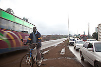 A cyclist passes stalled cars in a traffic jam on Thika road.