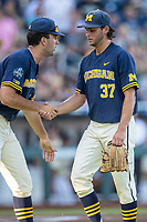 Michigan Wolverines pitcher Karl Kauffmann (37) is greeted by teammate Jack Bredeson (34) after completing an inning against the Vanderbilt Commodores during Game 3 of the NCAA College World Series Finals on June 26, 2019 at TD Ameritrade Park in Omaha, Nebraska. Vanderbilt defeated Michigan 8-2 to win the National Championship. (Andrew Woolley/Four Seam Images)