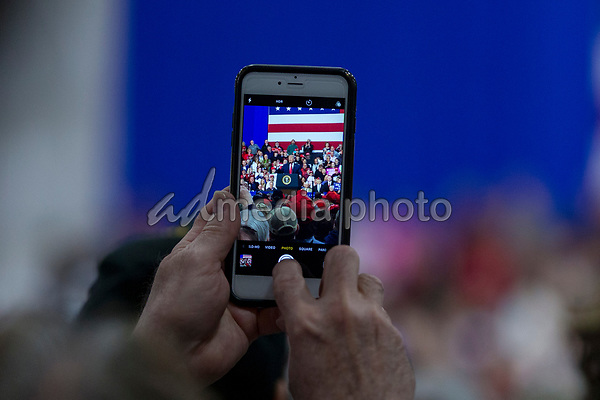 A supporter takes a cell phone picture as United States President Donald J. Trump speaks during a Make America Great Again campaign rally at Atlantic Aviation in Moon Township, Pennsylvania on March 10th, 2018. Photo Credit: Alex Edelman/CNP/AdMedia