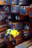 Abstract, overhead view of stacked and numbered iron billets and bright yellow work gloves. Texas.