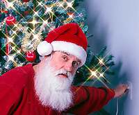 Santa plugs in the lights of the Xmas tree.  Model Release.