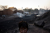 A child looks on while raw coal is burnt to process the coal in Borapahari in Jharia, Jharkhand, India. Coal fires rage just below the surface of the ground, making it too hot to walk with naked feet, noxious gases spew up from fissures, making the environment toxic. Residents who live above the furnace make $2 a day collecting small chunks of coal they sell to illegal middlemen. One or two houses collapse annually into vast underground caverns left unfilled by abandoned mining operations. Photo: Sanjit Das