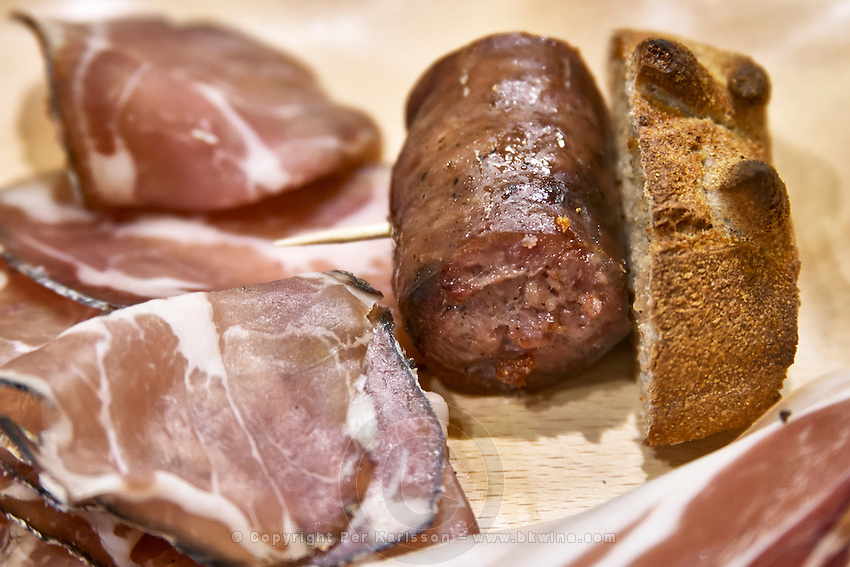 Corsica style charcuteries, smoked and dried ham, sausages on a wooden cutting board, Corsica, France
