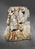 Roman Sebasteion relief sculpture of  an Imperial prince as Diokouros son of zeus, Aphrodisias Museum, Aphrodisias, Turkey.  Against a grey background.<br /> <br /> An imperial youth wearing a military cloak and cuirass of a commander holds the reins of hios horse. This panel is next to a Claudius panel so is probably of Britanicus or Nero the emperors son and intended successor