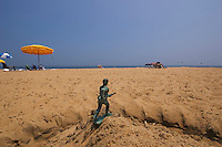 Toy soldier stands guard in the sand at the beach