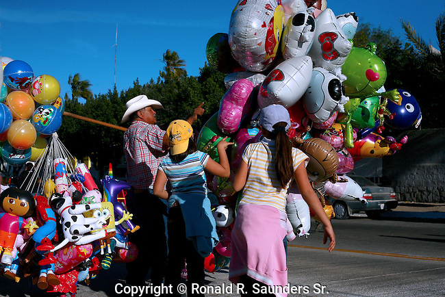 Boy and girl select balloons from vendor