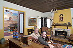 A living room with two males sitting with their dog, fireplace, chandelier, and windows. California