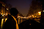 A woman rides in a boat through the canals at night in Amsterdam, the Netherlands.