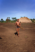 Pavuru Village, Brazil. Man with bow and arrows and reddened hair outside a palm thatch house. Cinta Larga tribe.