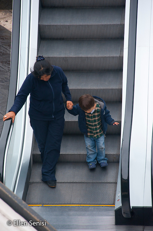 Lima, Peru. Miraflores district, Larcomar Mall.  Mother and son (young child, Peruvian) go down escalator together. No MR. ID: AL-peru.