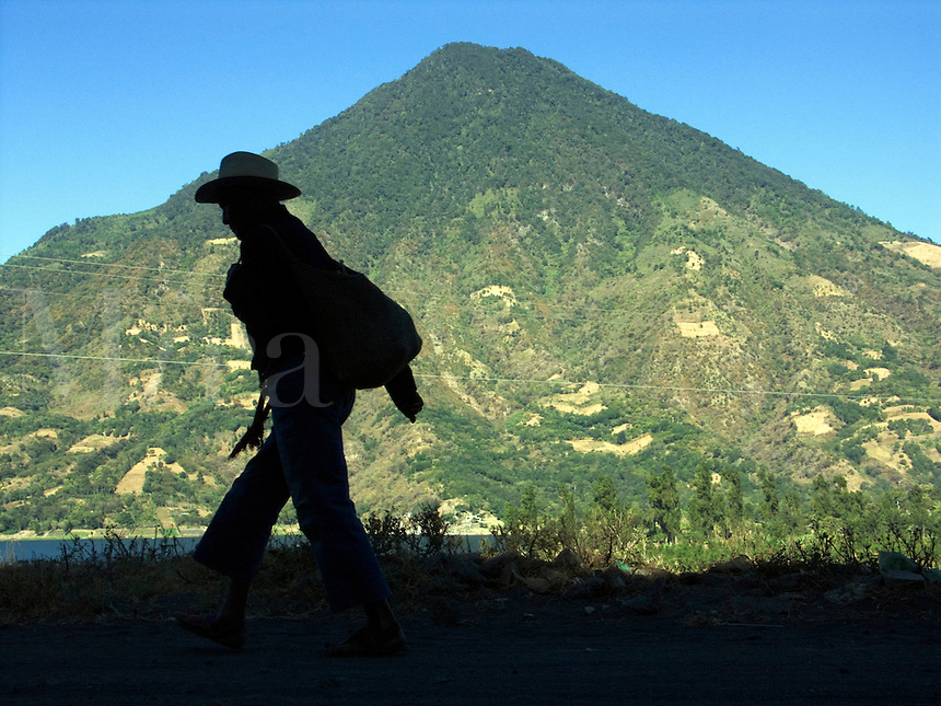 In Santiago Atitlan, in the highlands of Guatemala, coffee farmers and local people walk to work beneath a towering volcano.<br />