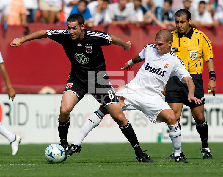 Real Madrid defender (3) Pepe tries to tackle the ball away from DC United midfielder (8) Andrew Jacobsen during their friendly at FedEx Field in Landover, Maryland.  Real Madrid defeated DC United, 3-0.