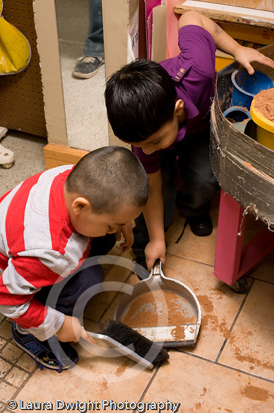 Preschool Headstart 3-5 year olds clean up two boys working together is use dust pan and hand broom to sweep up spilled sand vertical