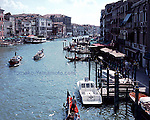 Photo of the Grand Canal viewed from the Rialto Bridge showing many mooring posts for the gondolas and other boats on the side opposite to the quayside. Two boats in the center of the canal a well as a gondola with a couple in the foreground. Travel photo of Venice, Italy by Tomoko Yamamoto. Original on 120 slide film by Mamiya 6 (Medium Format).