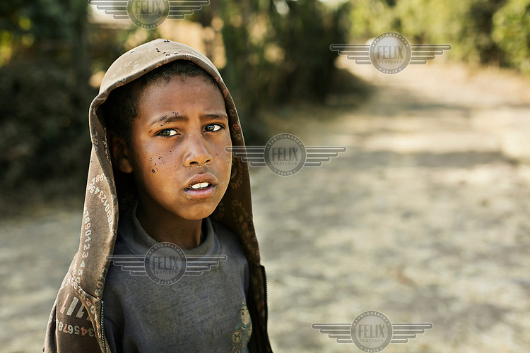 A boy heads home after a day herding cattle.