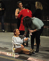 Pictured: A woman sits on the pavement in the early hours of Saturday, 17 December, 2016<br />