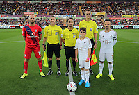 Pictured: Child mascot with team captains Russell Penn of York (L) Leon Britton for Swansea (R), match referee James Adcock (C) and linesmen T Wood and D Robathan Tuesday 25 August 2015<br /> Re: Capital One Cup, Round Two, Swansea City v York City at the Liberty Stadium, Swansea, UK.