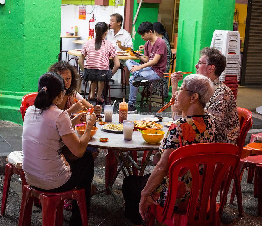 Family Having Dinner at Sidewalk Restaurant at Night, Ipoh, Malaysia.