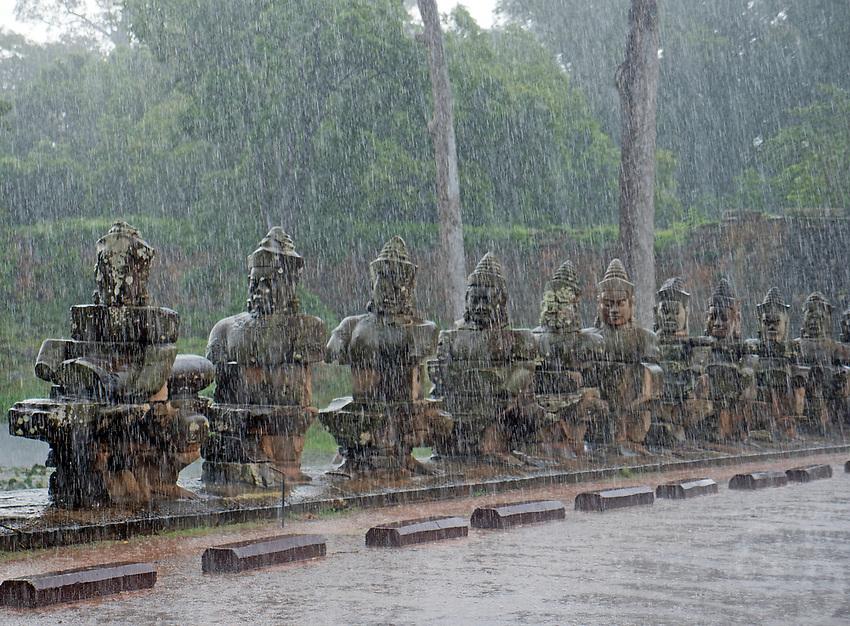 Heavy Monsoon rain over the stone faces at the entrance bridge and gate near Bayon Temple. Cambodia