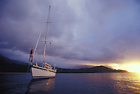 Woman on bow of sailboat at sunset, at anchor in Hanalei Bay, North Shore of Kauai, Hawaii