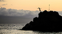 A cliff diver starting his dive off of Black Rock during a sunset show hosted by a resort, Ka'anapali Beach, Maui.