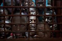Juvenille inmates look through the bars of their cell door in Pademba Central Prison. By law, minors cannot be incarcerated with older prisoners, but there are twenty children in the prison serving sentences ranging from 18 months to 4 years. Many of them suffer violence and sexual exploitation. They have no access to formal education and family visits are rare or non-existent..