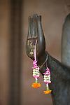 Ventiane. Offrandes sur une statue des pagodes Vat Sisaket. . Laos .