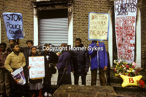 New Cross, London. 1981<br /> Locals gather outside the house where 13 young adults died in a devastating house fire during a birthday party on Sunday 18 January 1981. The London Metropolitan Police were accused of covering up the cause, which they suspected was an arson attack motivated by racism. Nobody has ever been charged in relation to the fire.