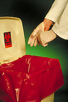 A close-up shows hands of medical employee taking medical gloves off and disposing them in proper medical waste container. Medical worker.