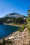 Lassen Peak, seen here over Lake Helen, is one of the worlds largest plug dome volcanoes, and last erupted in May, 1914.  Called a miniature Yellowstone by many, mud pots, fumaroles and boiling water continue to this day.  Lassen is part of the Pacific Ring of Fire.  This view is from the Lake Helen shore along Highway 89, which traverses the park, looks east toward Juniper Lake and Snag Lake.