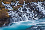 Hraunfossar (Borgarfjörður, western Iceland) is a series of waterfalls formed by rivulets streaming over a distance of about 900 metres out of the Hallmundarhraun, a lava field which flowed from an eruption of one of the volcanoes lying under the glacier Langjökull. The waterfalls pour into the Hvítá river from ledges of less porous rock in the lava. The name hraun comes from the Icelandic word for lava.