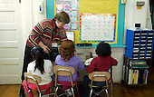 MR / Schenectady, NY.Yates Arts in Education Magnet School, Grade Two.Teacher prepares students and equipment for reading activity at listening center. Teacher has organized learning centers so students can vary their activities during reading group time instead of relying on textbooks only for reading curriculum..MR: Car19 g2c.© Ellen B. Senisi