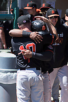 San Jose Giants center fielder Heliot Ramos (13) is hugged by Ryan Kirby (10) after hitting a home run during a California League game against the Stockton Ports on April 9, 2019 in Stockton, California. San Jose defeated Stockton 4-3. (Zachary Lucy/Four Seam Images)