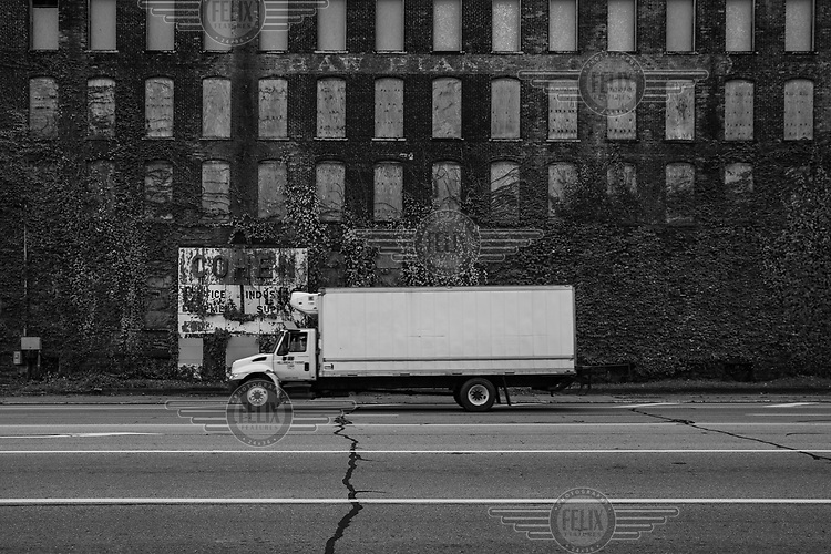 A truck passes an abandoned factory building slowly being covered in ivy.