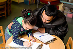 Educaton preschool  3-4 year olds start of day father with daughter as she signs herself in at beginning of day Hispanic horizontal