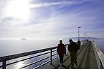 Seniors Walking on Fishing Pier, Des Moines, Washington, USA.  Puget Sound in background.