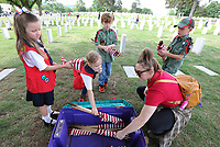 Brittany Maples (right), troop vice-coordinator with the American Heritage Girls, collects flags Friday, June 4, 2021, as she volunteers with Bo's Blessing at the National Cemetery in Fayetteville. More than 8,000 flags, provided by the National Cemetery Organization, were posted on the grave sites in recognition of Memorial Day. The flags are dried, rolled up and then stored for future use. Check out nwaonline.com/210605Daily/ and nwadg.com/photos for a photo gallery.<br /> (NWA Democrat-Gazette/David Gottschalk)