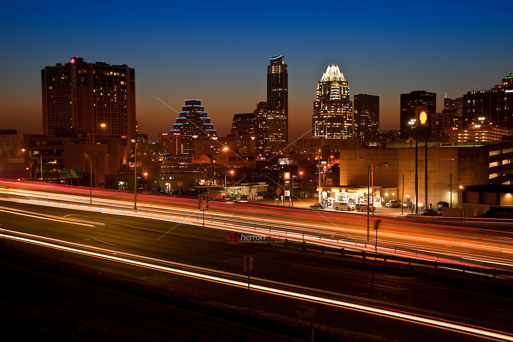 Austin traffic passes by the bustling Downtown Cityscape at Sunset.