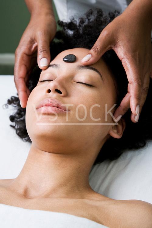 USA, California, Oakland, young woman receiving stone spa treatment