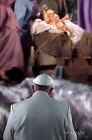 Pope Francis prays in front of a Nativity scene in St Peter's square at the Vatican  on December 31, 2016